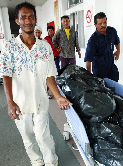 Mohd Zani ketika mengiringi jenazah isterinya di bilik mayat