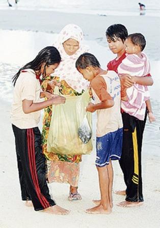 Mek Som bersama cucunya melihat hasil jualan di Pantai Melawi